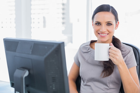 Cheerful attractive businesswoman drinking tea in her office photo