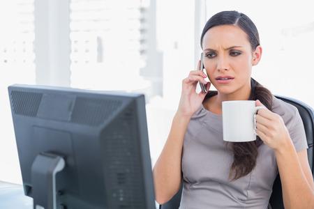 answering phone: Con el ce�o fruncido empresaria caf� celebraci�n y contestar el tel�fono en su oficina
