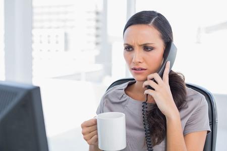 answering phone: Con el ce�o fruncido secretaria tel�fono de respuesta en su oficina