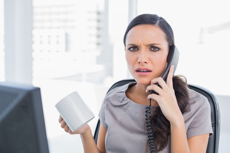answering phone: Secretario Irritado contestar el tel�fono en su oficina Foto de archivo