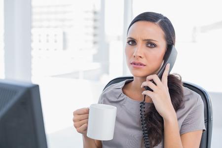answering phone: Secretaria preocupante contestar el tel�fono en su oficina Foto de archivo