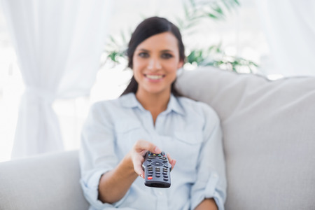 changing channel: Cheerful attractive brunette changing tv channels in living room