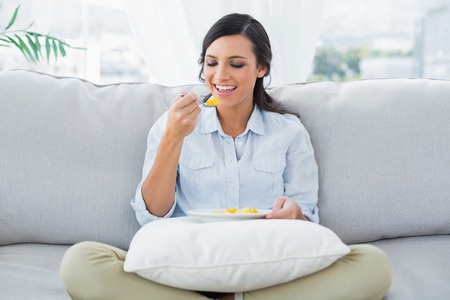 crossing legs: Cute woman sitting on the couch crossing legs eating fruits in her living room