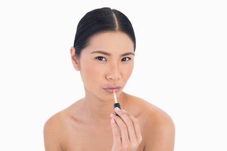 Sensual young model applying lip gloss on white background photo