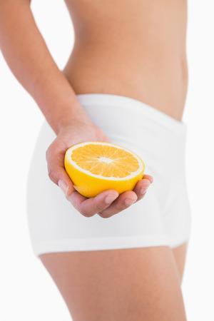 with orange and white body: Cuerpo femenino virada explotaci�n media naranja sobre fondo blanco Foto de archivo