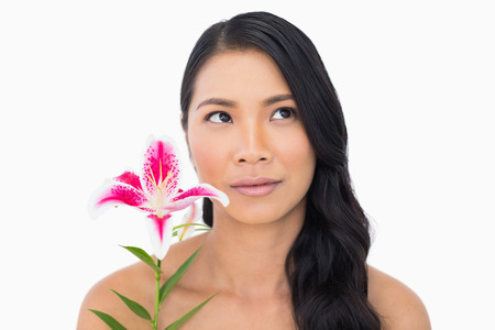 Pretty natural brown haired model holding lily on white background photo