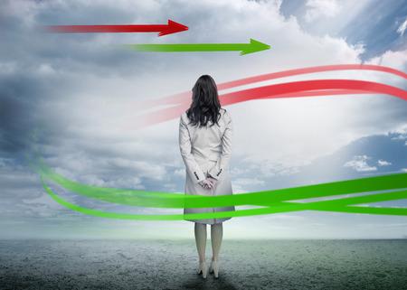 mujer mirando el horizonte: Empresaria busca en flechas rojas y verdes en el soleado paisaje des�rtico