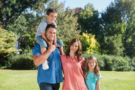 Cute family smiling at camera in the park on a sunny day photo