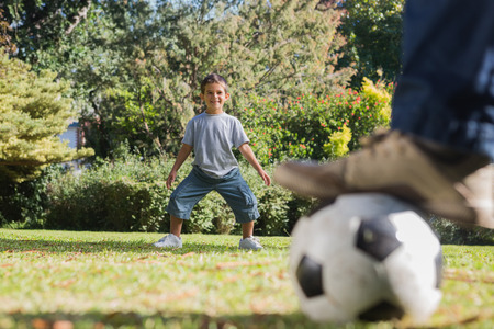 goal keeper: Son standing as goal keeper with dad in the park Stock Photo