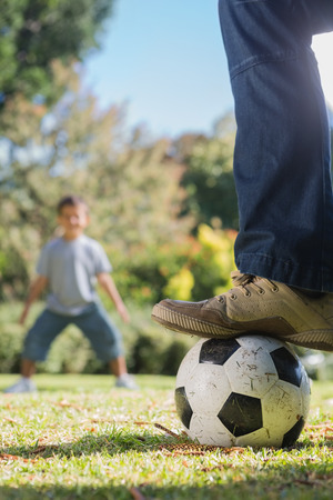 Child waiting for the football under fathers foot in the park photo