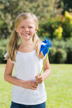Blonde girl smiling and holding pinwheel in the park on sunny day photo