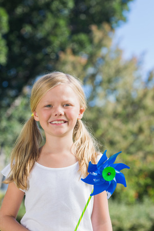 Cute blonde girl holding pinwheel smiling at camera in the park in sunshine photo