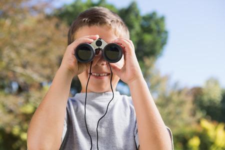 Boy looking through binoculars in the park