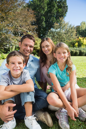 Cheerful family relaxing outside in the park smiling at camera photo