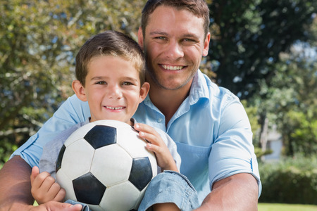 Happy dad and son with a football in a park smiling at camera photo