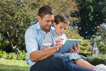 Dad and son using a tablet pc in a park on sunny day photo