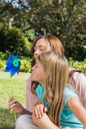 Mother with daughter blowing pinwheel in the park on summers day photo