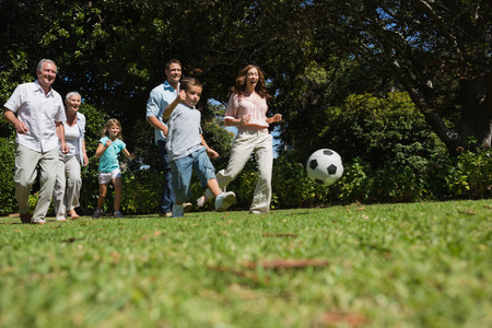 kick ball: Cheerful multi generation family playing football in the park