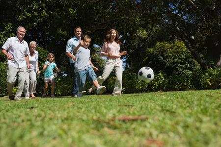 jugando futbol: Familia multi generaci�n alegre jugando al f�tbol en el parque Foto de archivo