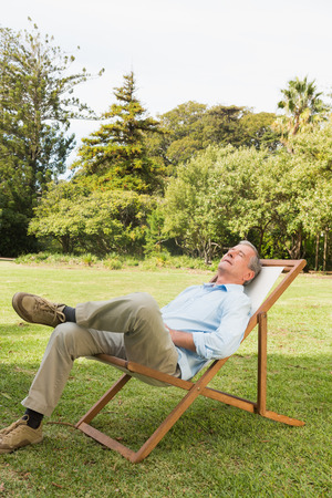 Happy man resting in sun lounger at park photo