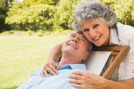 Smiling mature man lying on sun lounger and behind him his wife photo