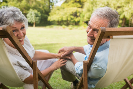 Happy mature couple smiling and looking at camera in park on deck chairs photo