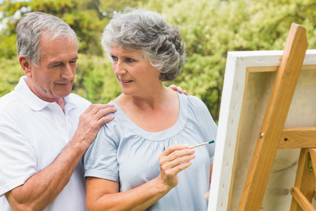 Cheerful retired woman painting on canvas and talking with husband in the park on sunny day photo