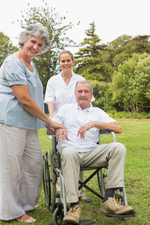 Man in wheelchair and his wife and nurse in park smiling at camera photo