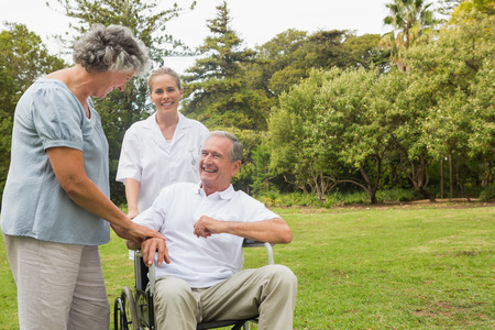 Happy man in a wheelchair laughing with his nurse and wife on sunny day in park photo