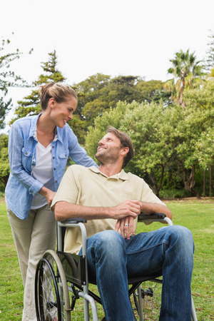 Happy man in wheelchair talking with partner in the park on a sunny day photo