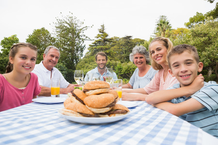Extended family eating outdoors at picnic table smiling at camera photo