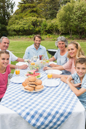 Cheerful extended family having dinner outdoors at picnic table smiling at camera photo