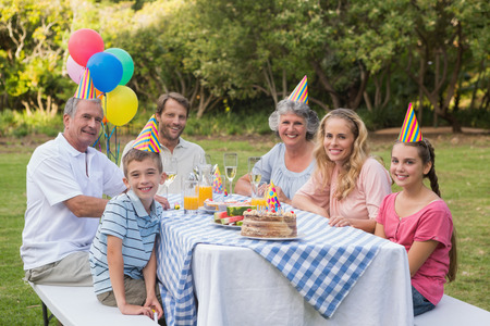 Family smiling at camera at birthday party outside at picnic table photo