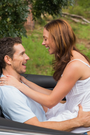Young couple feeling romantic in back seat and laughing in a convertible in countryside photo