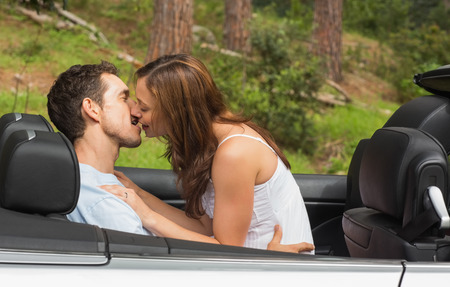 Young couple smooching on the backseat of a convertible photo
