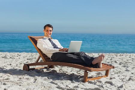 ejecutivos: Sonriente joven hombre de negocios en la playa tumbado en una tumbona con su computadora portátil