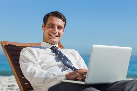 context: Cheerful young businessman on the beach lying on a deck chair with his computer