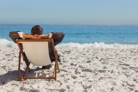 vacaciones playa: Hombre de negocios joven se relaja en su hamaca en la playa