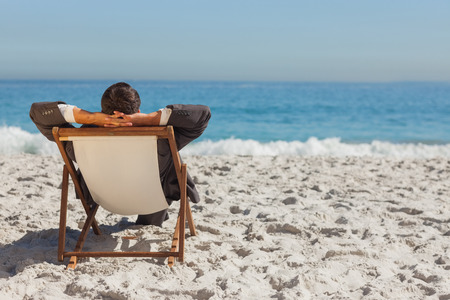 escapism: Young businessman relaxing on his sun lounger on the beach