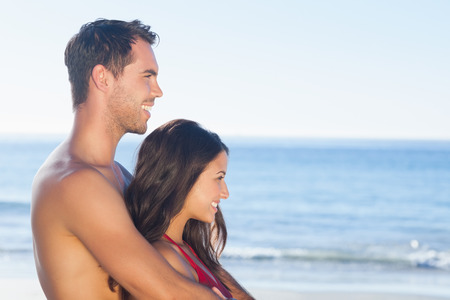 Happy couple in swimsuit on the beach hugging while looking at the water