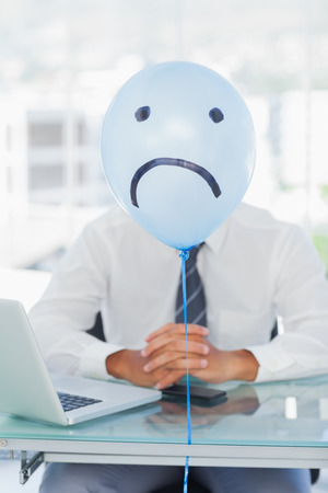 sad face: Blue balloon with sad face hiding businessmans face in bright office