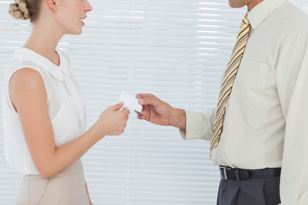 Business people exchanging business card in bright office
