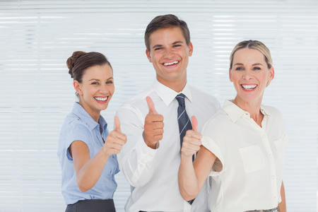 Cheerful colleagues posing with thumbs up in bright office photo