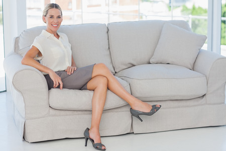 woman legs: Attractive blonde businesswoman posing sitting on sofa in bright office
