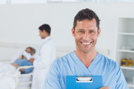 Portrait of surgeon in bright surgery with doctor attending patient on background photo