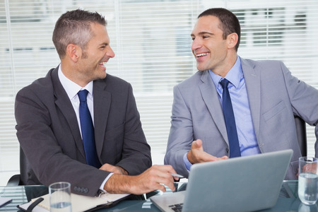 Cheerful businessmen laughing while working in bright office photo