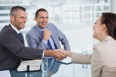 Handshake business: Cheerful young woman shaking hands with her future employer in bright office