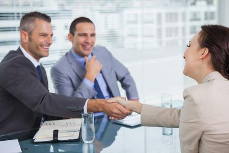 estrechando mano: Mujer joven alegre dando la mano a su futuro empleador en la Oficina brillante Foto de archivo