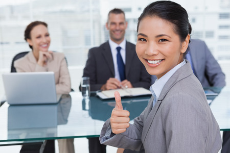 Young applicant in bright office giving thumb up after obtaining the job photo