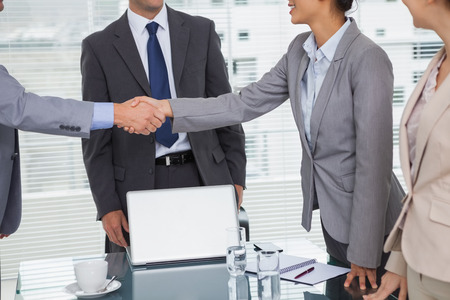 Business people meeting and shaking hands in bright office photo